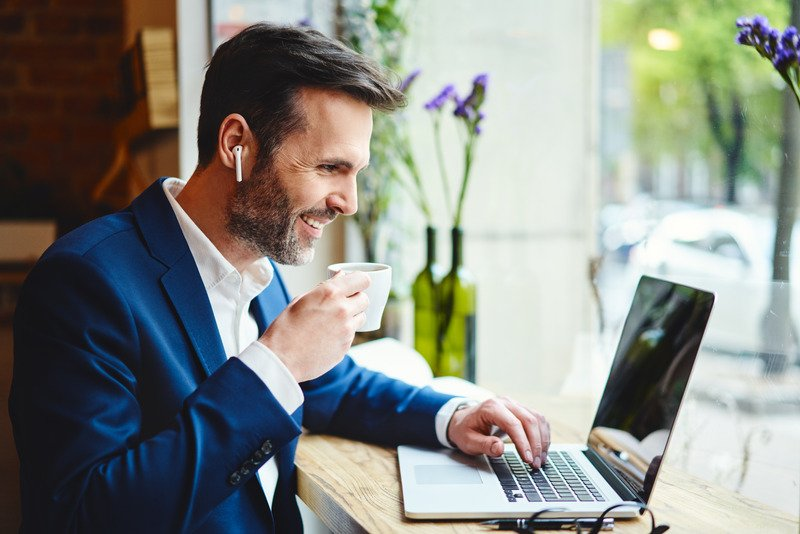 Canva - Businessman having videocall on laptop while drinking coffee in cafe (1)